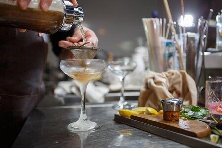 behind: Bartender coocks cocktail behind a bar counter Stock Photo