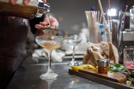 Bartender coocks cocktail behind a bar counter Banque d'images