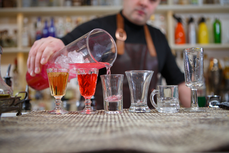 shooter drink: Bartender pours various of alcohol drink into small glasses on bar