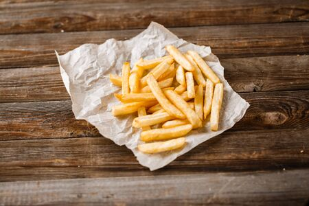 rustic kitchen: French fries on wooden table. Top view.