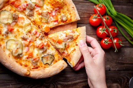 high calorie: Hand picking tasty slice of pizza lying on wooden table, Focused on hand. Stock Photo