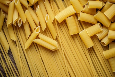 talian: Close up mix of raw dried talian pasta, macaroni, spaghetti, penne on wooden table.  Top view