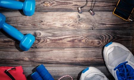 Sport spullen op houten tafel, bovenaanzicht. Lichte plek in het centrum van de houten tafel met lege ruimte voor tekst, logo, of iets anders. Stockfoto