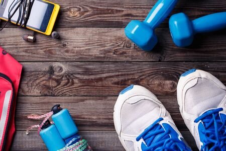 Sports equipment - sneakers, skipping rope, dumbbells, smartphone and headphones. Sport background on wooden floor, top view. Stock Photo