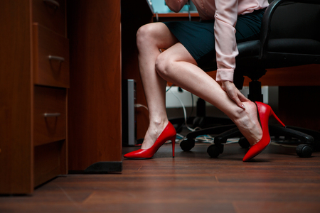 feet on desk: Business woman touching feet with her hand. Stock Photo