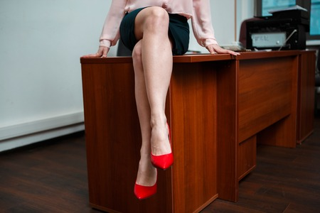 provocative couple: Sexy businesswoman sitting on table at office. Stock Photo
