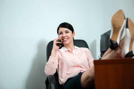footrest: Relaxed business woman sitting in a chair with legs over the table and talking over phone. Stock Photo