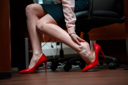 touching toes: Business woman touching feet with her hand. Stock Photo