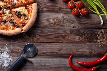ingridients: Tasty pizza with ingridients on a wooden board. Top view with empty space in center Stock Photo