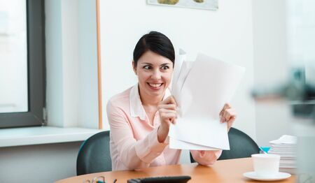 unsuspecting: Woman in office with crumpled paper. Office life concept. Stock Photo