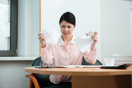 uninspired: Woman in office with crumpled paper. Office life concept. Stock Photo