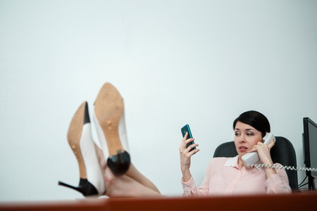 footrest: Relaxed business woman sitting in a chair with legs over the table.