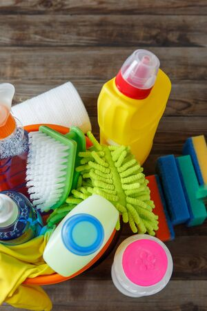 cleaning supplies: Plastic bucket with cleaning supplies on wood background. Stock Photo