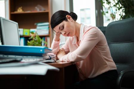 inefficient: Tired businesswoman sleeping on the desk.