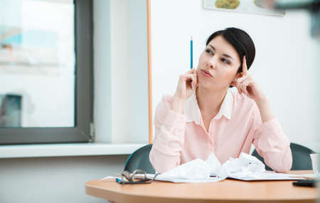 speculative: Businesswoman sitting at desk in the office in thoughts.