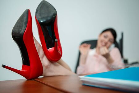 footrest: Relaxed businesswoman with legs on the desk