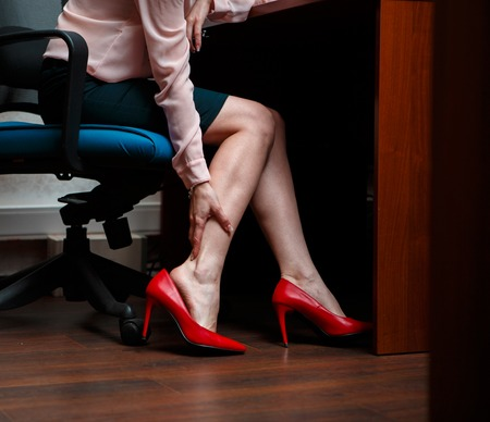 tired: Business woman touching feet with her hand. Stock Photo