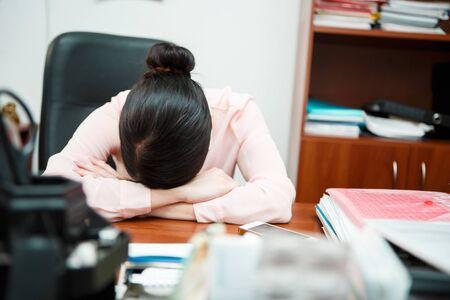 portable failure: Tired businesswoman sleeping on the desk.
