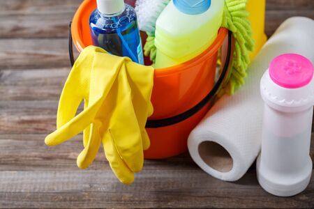 cleaning supplies: Plastic bucket with cleaning supplies on wood background