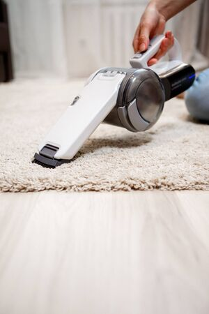 cordless: Female hand holding small white cordless vacuum cleaner and cleaning rug indoors