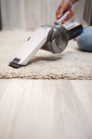 Female hand holding white small cordless vacuum cleaner and cleaning beige carpet on beige parquet. Device closeup at home