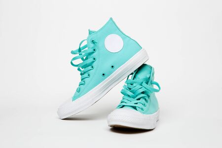 Turquoise sneakers with laces on blank white background