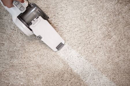 carpet clean: Dusty carpet and clean stripe after clearing cordless handheld vacuum cleaner