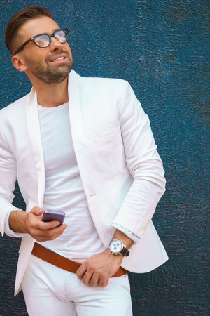 white suit: Stylish portrait of young man in white suit with phone in hand
