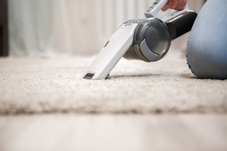 Woman in blue jeans on her knees cleaning carpet