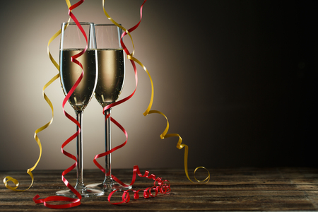 Two champagne glasses on table decorated yellow and red ribbons. Image on black background with backlight Stock Photo