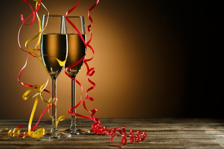 Two glasses of champagne decorated with gold and red streamer on black background with backlight and copy space