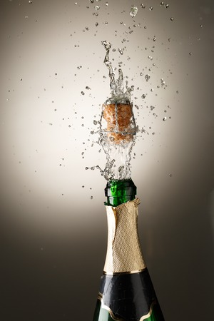 popping the cork: Champagne bottle with cork popping and splash. Celebration theme
