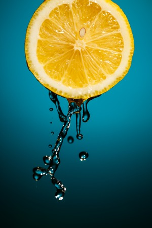 intentional: Fresh water drops on lemon isolated on background with intentional vignette