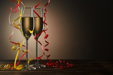 Two glasses of champagne decorated with gold and red streamer ready to party Stock Photo