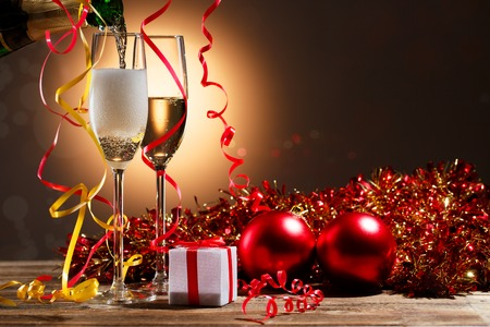 uncork: Champagne pouring from bottle into glasses on the background of Christmas decorations