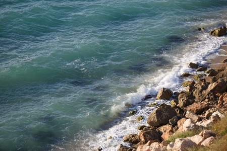 shorelines: Wild beach with rocky shore and pure black sea. Picturesque sea view on sunny day