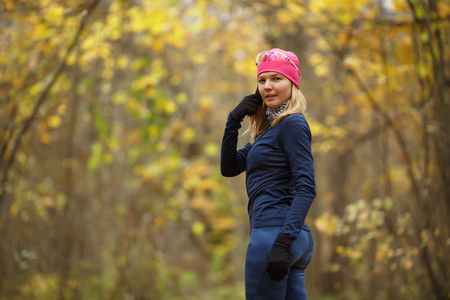 Smiling girl in pink hat on background of autumn landscape