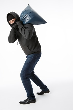 Thief in black mask with bag on his shoulder on pure white background
