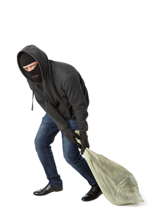Thief in black gloves drags heavy bag on pure white background Stock Photo