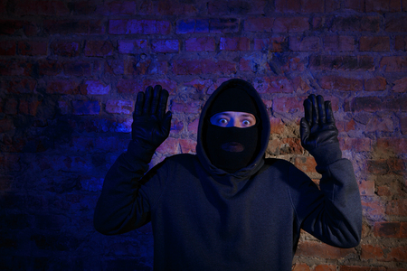 law breaking: Surprised thief standing with hands up against brick wall
