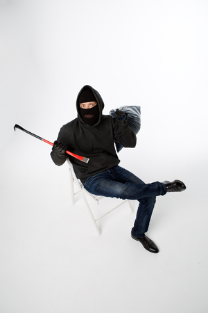 Robber sitting on white chair with bag and lock pick empty white wall