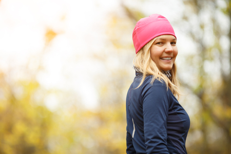 Smiling girl in pink hat standing in autumn forest.