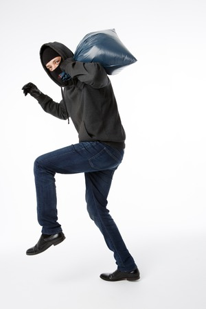 Thief in black gloves with bag on his shoulder sneaks on empty white background