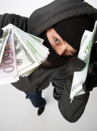sneaks: Burglar in black mask with money in hand on blank white background view from above