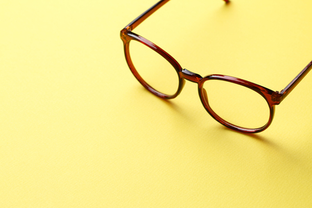 optician: Brown glasses with clear lenses on yellow empty background