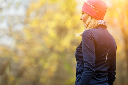 Sport girl standing back in autumn forest .Image with lens flare effect