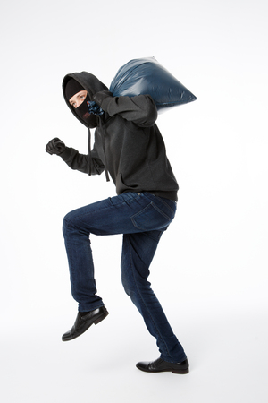 Thief slinking with blue bag on pure white background Stock Photo