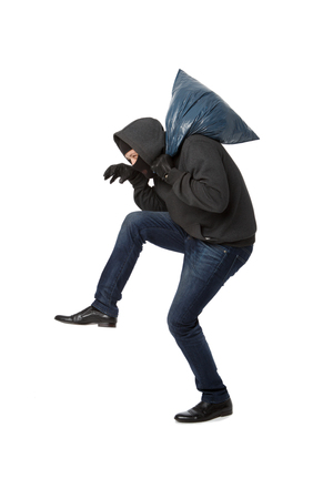 Robber sneaks with blue bag on his shoulder on blank white background Stock Photo