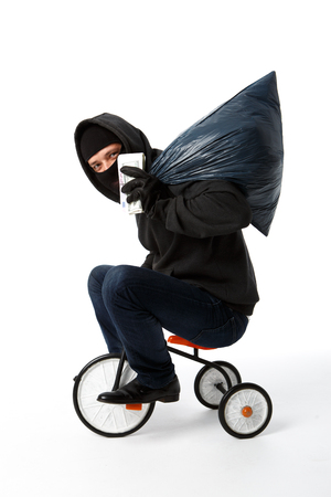 Burglar coming on childrens bike with pack of money on empty white background Stock Photo