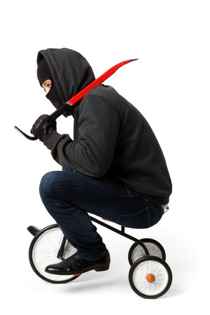 Burglar going with master key on little childrens bicycle on pure white background Stock Photo